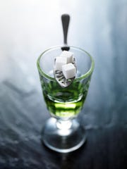 Absinthe in a traditional pontarlier glass awaits dilution by cold water dripped onto sugar cubes.