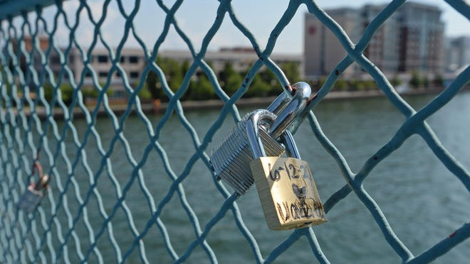 """A few of the many love locks are shown attached to second-floor fencing at Dobbins Landing near Bicentennial Tower and the mural """"Flotsam"""" by international artist SatOne."""