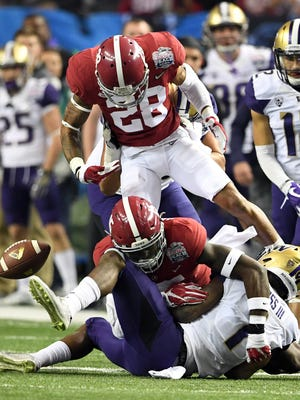 Washington Huskies wide receiver John Ross (1) fumbles against the Alabama Crimson Tide during the first quarter in the 2016 CFP semifinal at the Peach Bowl at the Georgia Dome.