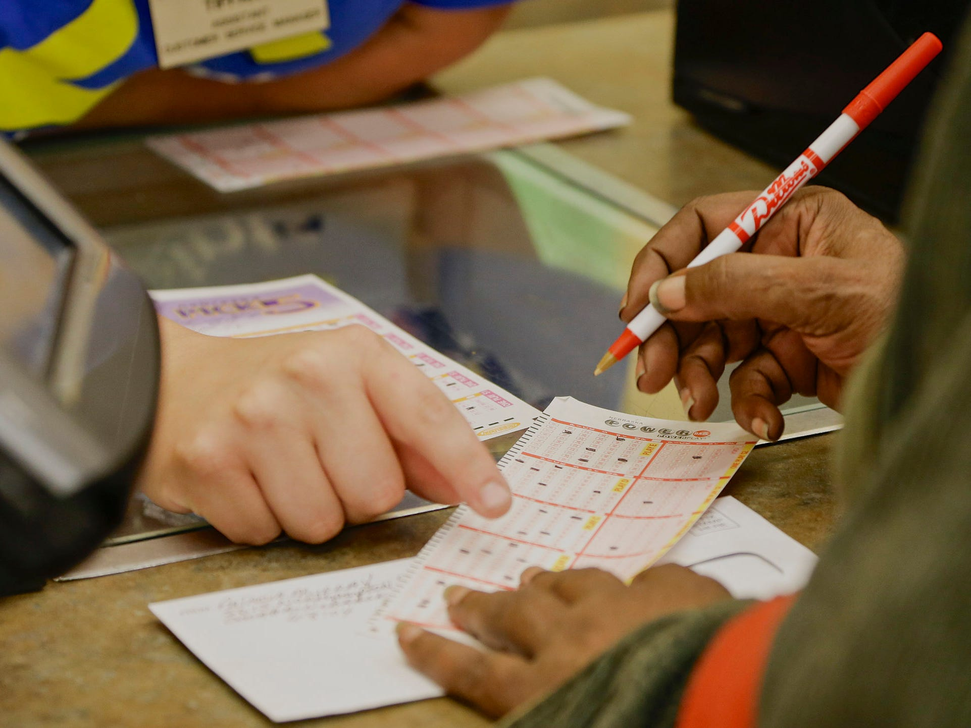 A customer fills out her powerball form at a Baker's supermarket in Omaha, Neb.