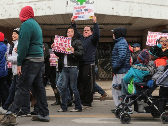Hundreds of people march along W. Vernor Hwy. in Detroit