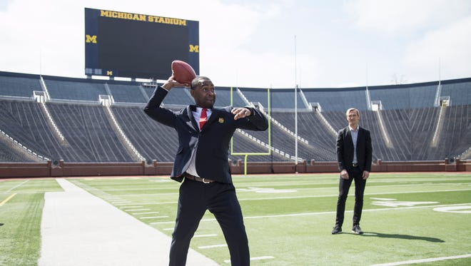 Manchester United F.C. legend Andrew Cole, tries to throw a football at the Michigan Stadium in Ann Arbor, Wednesday, April 18, 2018. Behind him is Liverpool F.C. legend Sami Hyypia.