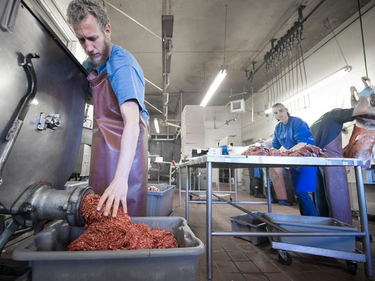 Derek Knaub grinds venison burger at J. L. Miller &