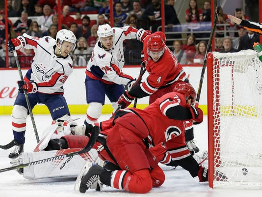 Washington Capitals' Lars Eller (20), of Denmark, assists as John Carlson (74) scores against Carolina Hurricanes goalie Cam Ward while Hurricanes' Haydn Fleury (4) and Jaccob Slavin defend during the first period of an NHL hockey game in Raleigh, N.C., Friday, Jan. 12, 2018. (AP Photo/Gerry Broome)
