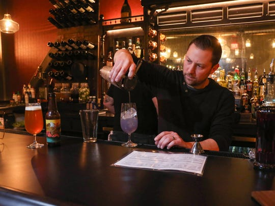 Daniel Smith, co-owner at Juniper Moon, on Ingersoll Ave. in Des Moines, mixes a Juniper Moon drink.