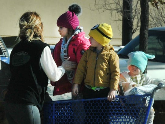 A shopping cart of bundle up kids is unloaded from the Academy parking Thursday afternoon with daytime high temperatures expected in the low 40's. Friday's temperatures leading into the weekend will range from mid-50's to upper 60's by Sunday.