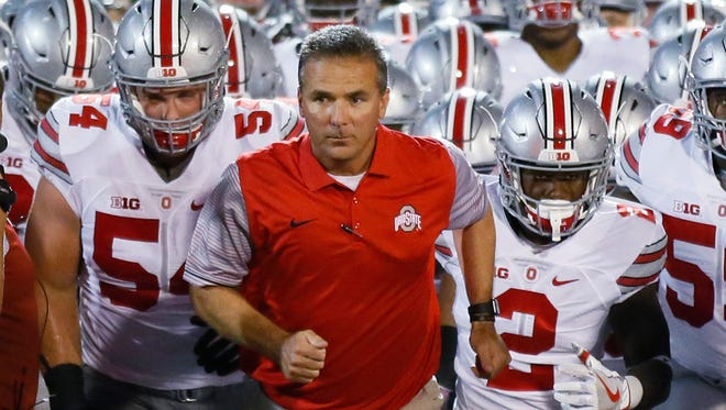 Ohio State coach Urban Meyer leads his team onto the field for an NCAA college football game against Oklahoma in Norman, Okla., Saturday, Sept. 17, 2016. Ohio State won 45-24. (AP Photo/Sue Ogrocki)