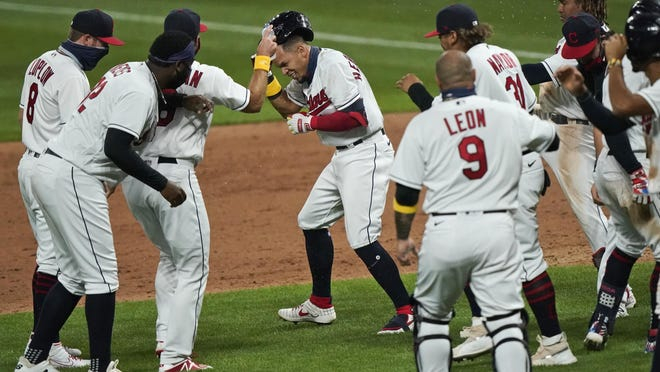 Cleveland Indians' Cesar Hernandez, center, is mobbed by teammates after hitting an RBI-single in the ninth inning in a baseball game against the Milwaukee Brewers, Saturday, Sept. 5, 2020, in Cleveland. The Indians won 4-3.