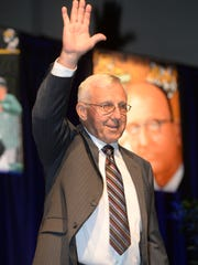 Jim Hightower waves as he walks up on stage during
