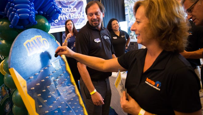 """Vice President of First Florida Integrity Bank Douglas Tice, center, watches as passers-by play a game of """"Banko"""" during the Connections Expo at The Naples Grande Beach Resort on Tuesday, Aug. 22, 2017, in North Naples."""