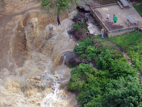 Visitors watch the raging water of Mill Creek Saturday afternoon at the Cataract Falls State Recreation Area in Owen County. (From WTHR Chopper 13)