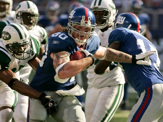 FILE - In this Oct. 7, 2007 file photo, New York Giants' Jeremy Shockey breaks free of a tackle attempt by New York Jets' Kerry Rhodes to score a touchdown during the third quarter of an NFL football game in East Rutherford, N.J.,  Sunday, Oct. 7, 2007. The Jets and Giants are preparing for their first regular-season showdown on Sunday, Dec. 6, 2015, since 2011. (AP Photo/Ed Betz, File)