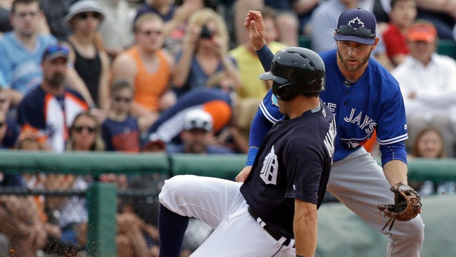 The Detroit Tigers' Ian Kinsler, left, slides into third base as the ball gets by Toronto Blue Jays infielder David Adams in the first inning Tuesday, March 29, 2016, in Lakeland, Fla.