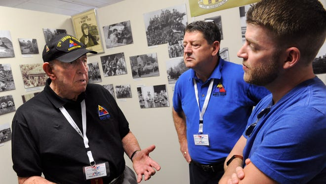 World War II veteran George Rich describes part of his time serving with the 12th Armored Division to his son Jim and grandson Jonathan Friday July 21, 2017 at the division's museum. This weekend's 12th Armored reunion marks the 75th anniversary of the division's activation.