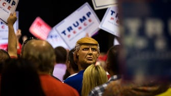 A man wears a Donald Trump mask backwards in Tampa on Aug. 24, 2016.