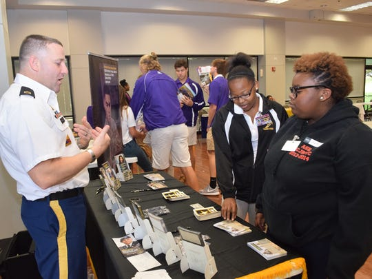 Alexandria Senior High School seniors Crystal Easter (right) and Shanyah Hodge, visit with U.S. Army recruiter Staff Sgt. Kenneth Hagood at a Rapides Parish college fair at Louisiana College on Thursday.