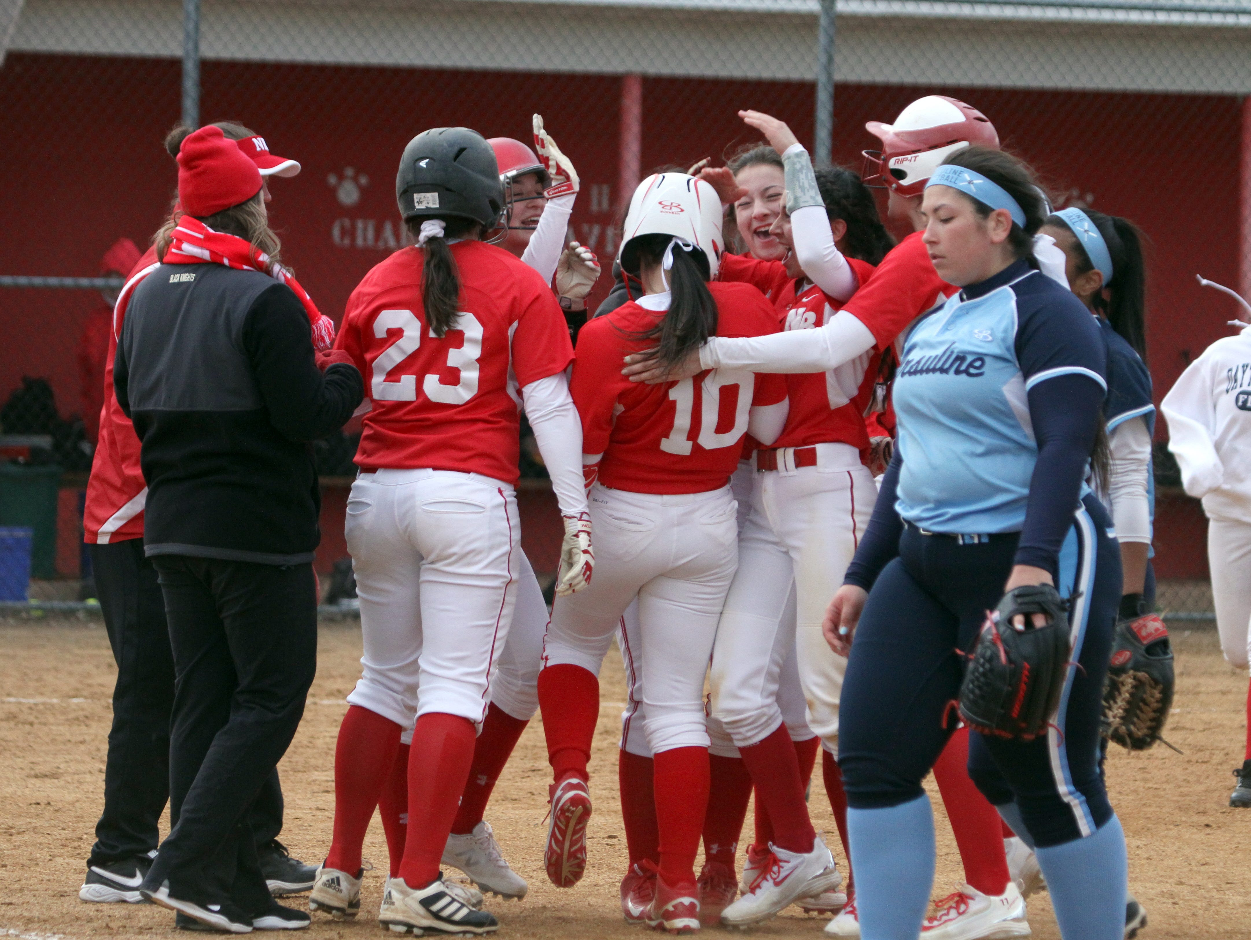 Ursuline pitcher Val Cucci walks off the field as North Rockland's Kayla McDermott is mobbed by teammates after hitting the game winning hit in the bottom of the 7th inning of a varsity softball game at North Rockland High School April 7, 2016. North Rockland defeated Ursuline 6-5.