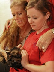 Bonnie Butterworth, left, pets Lucky the cat, who is