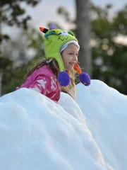 Skyla Norton, 6, plays on the snow mountain during Snowfest in Golden Gate on Dec. 3, 2016.