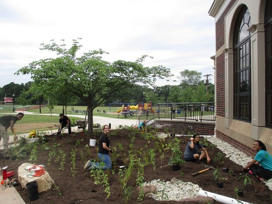 Highland Park High School students, under the supervision of the RCE Water Resources Program staff, got their hands dirty to help plant a rain garden with native plants that will be fed the water.