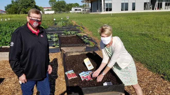 Mike Hogan and Ohio Department of Agriculture Director Dorothy Pelanda plant the first seeds in the demonstration fall victory garden at OSU.