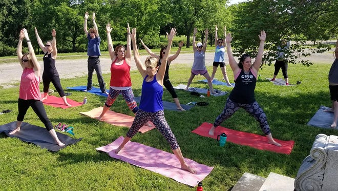 Yoga participants hold a pose during a class at Topeka Cemetery.