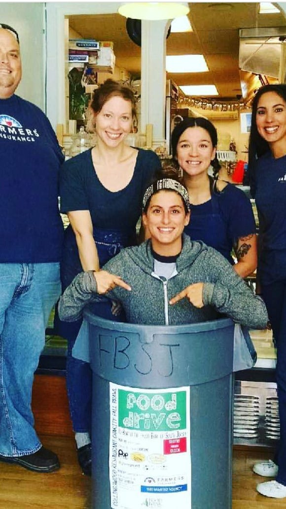 Charity Fall Brawl organizers Jason Rameriz (from left), Lyndsey Ferguson, Maura Rosato, Valentina Fortuna of Constellation Collective and Emily Oleaga-Talley of Rameriz Farmers Insurance gather round (and in) a Food Bank of South Jersey donation bin in 2016.