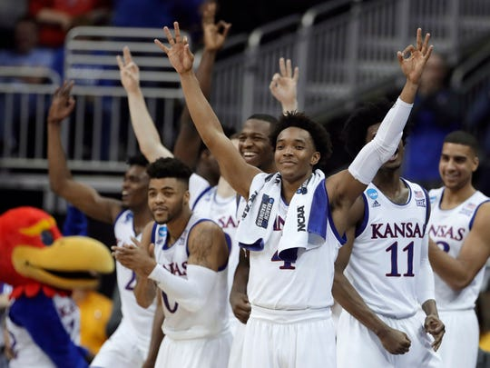 FILE - In this March 23, 2017, file photo, Kansas guard Devonte' Graham, center, celebrates with teammates during the second half of a regional semifinal against Purdue in the NCAA men's college basketball tournament, in Kansas City, Mo. Graham was named Big 12 player of the year, Tuesday, March 6, 2018. (AP Photo/Charlie Riedel, File)