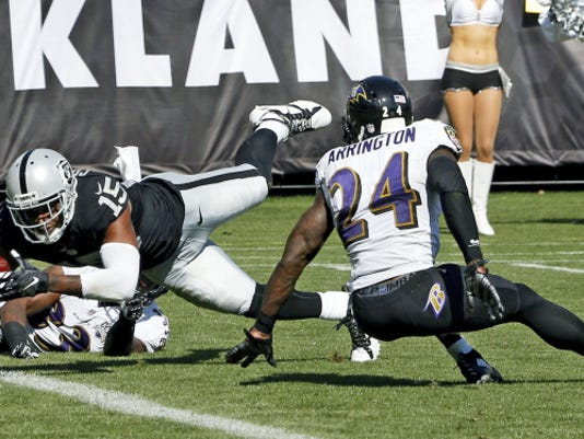 Oakland Raiders wide receiver Michael Crabtree (15) scores past Baltimore Ravens' Kyle Arrington (24) during the third quarter on Sunday in Oakland, California. The Ravens' defense struggled mightily in a surprising 37-33 loss to the Raiders.