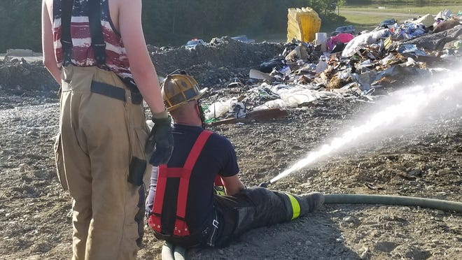 Bath firefighters work to extinguish a blaze at the Steuben County Landfill Thursday evening.