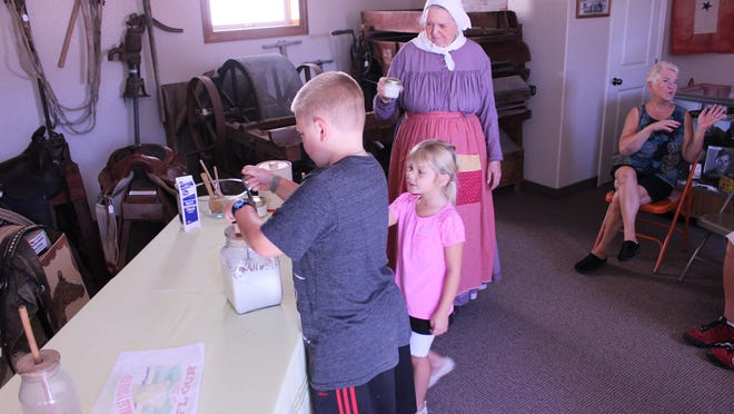 Landon Rothleutner churns butter while his sister, Heley, and Diana Coonradt observe.