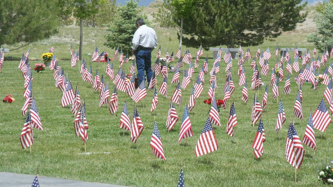 A man stands among a sea of American flags placed on graves to pay his respects after the Memorial Day ceremony Monday at the Northern Nevada Veterans Memorial Cemetery in Fernley.