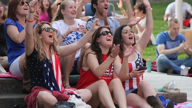 Emily Higgins, left, Becky Brand, center, and Kelsey Weidman cheer after a U.S. goal at Burlington's City Hall Park on Sunday.