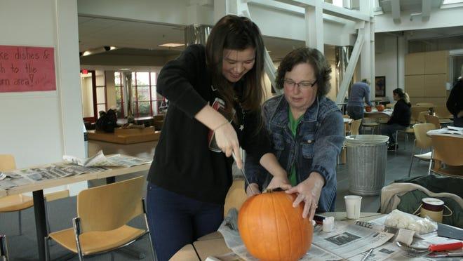 Reina Kurihara (left) cuts into a pumpkin with Tina Martin's help during the pumpkin carving event with Tomodachi families at Kaneko Hall on October 25.