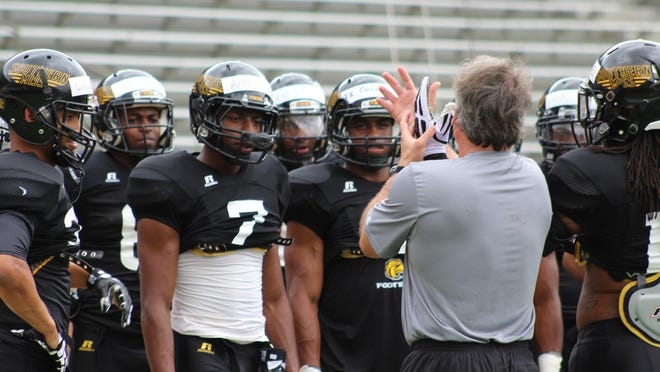 A group of Southern Miss defensive backs listen to football coach Jay Hopson during Thursday's practice session at M.M. Roberts Stadium.