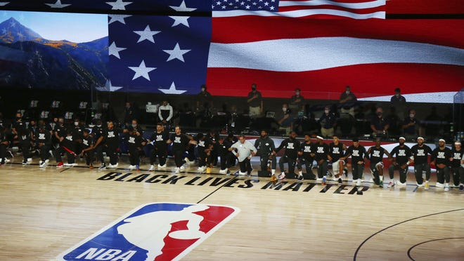 Utah Jazz and Los Angeles Lakers players and staff kneel during the national anthem before an NBA basketball game Monday, Aug. 3, 2020, in Lake Buena Vista, Fla.