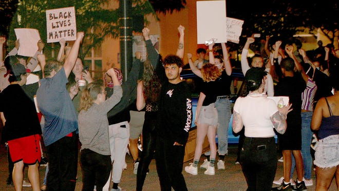 Protesters hold up their fists in solidarity.
