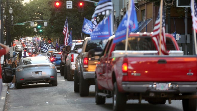 A caravan of supporters of President Donald Trump drive in downtown Portland, Ore., Saturday, Aug. 29, 2020. Saturday's rally was the third consecutive weekend that pro-Trump demonstrators converged in and around Portland, leading to clashes with counter protesters.