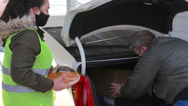Volunteers load boxes of food into a car Nov. 23 during Community Action House's Thanksgiving meal distribution in Holland. Fifteen percent of Michigan households said they were struggling to put food on the table during the pandemic, according to a report released Monday.