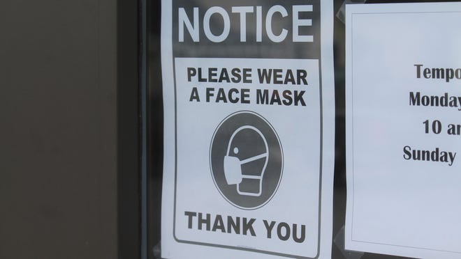 A sign asking customers to wear masks is on display at Minit Mart in Holland in May. Some business owners have grappled with mask enforcement since additional sectors of the economy have reopened.