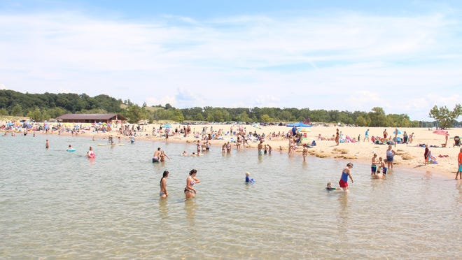People sit along and swim in Lake Michigan at Holland State Park in Holland. Local public safety officials are urging caution during all water-related activities.