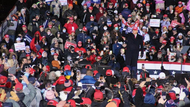 President Donald Trump waves to thousands of his supporters early Tuesday, Nov. 3, at Gerald R. Ford International Airport in Grand Rapids.