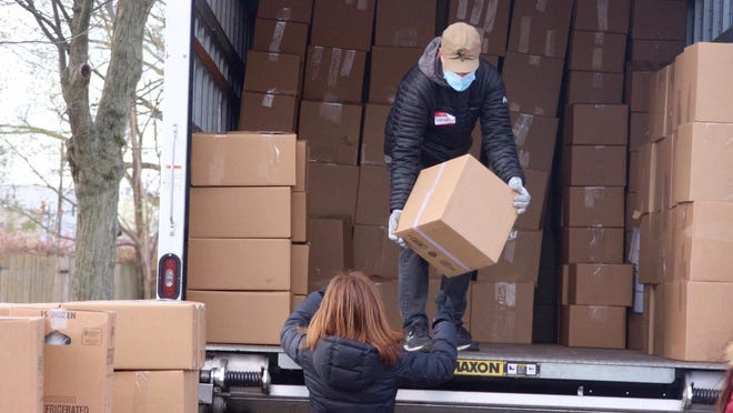 Volunteers unload boxes of food from a semi-truck Monday, Nov. 23, during Community Action House's Thanksgiving meal distribution.
