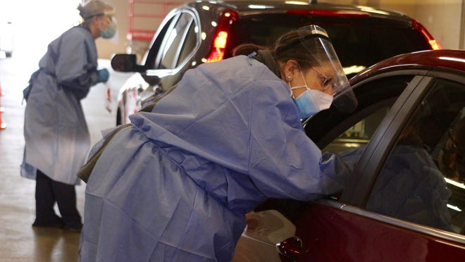Nurses perform COVID-19 nasal swab tests on patients Friday, Nov. 20, during the Ottawa County Health Department's COVID-19 drive-thru testing at the Ottawa County Road Commission.