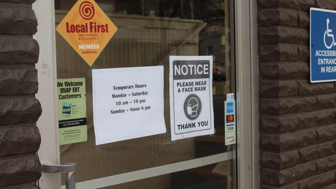 A sign asks customers to wear facemasks before entering Minit Mart's 15th Street location in Holland on Tuesday, May 19. Minit Mart owner Gregg Hill said the coronavirus pandemic has altered the way he operates his business.