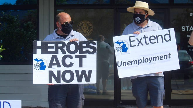 Protesters gather outside of U.S. Rep. Bill Huizenga's office in Grandville, Mich. on Thursday, July 23. The protesters called on the Zeeland Republican to support extending the federal government's unemployment benefits.