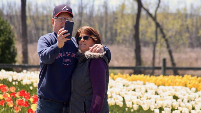 Nancy and Tom Lothamer of Grand Rapids snap a photo in front of the tulips May 6 at Windmill Island.