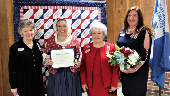 Alisa Crawford (center-left) is presented the DAR Women in American History Award by local DAR members Barbara Walker (left), Judith Hemwall (center-right) and Christina Saniga (right).