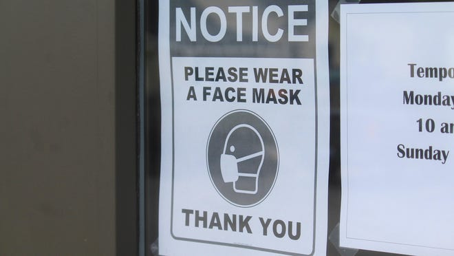 A sign asking patrons to wear masks is on display at the East Holland Minit Mart location in Holland, Mich., on Tuesday, May 19, 2020. The Ottawa County Department of Public Health issued a final cease and desist letter to a Hudsonville religious school on Oct. 22 over continued non-compliance with state health orders.