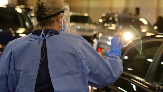 A nurse signals a driver to stop Friday, Nov. 20, during the Ottawa County Health Department's COVID-19 drive-thru testing at the Ottawa County Road Commission. As the coronavirus pandemic continues globally, health care workers are indicating they feel burned out by what they see at work.